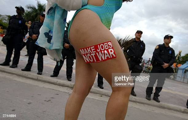 An antiglobalization protester poses in front of police November 19 2003 in Miami on the third day of the summit to create a Free Trade Area of the...