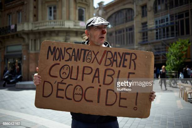An antiGMO activist holds a banner reading 'Monsantox/Bayer guilty of ecocide' during the International March against Monsanto which took place in...