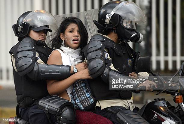 An antigovernment activist is arrested by national police during a protest against Venezuela President Nicolas Maduro government in Caracas on March...