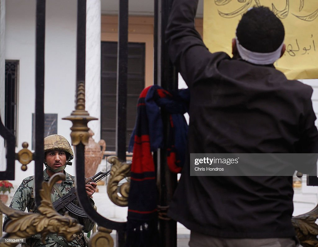 An anti-government protester attachs a sign to the gate of the Egyptian Parliament building while an Egyptian Army soldier watches from inside Feburary 9, 2011 in Cairo, Egypt. Thousands of Egyptians protested outside of the parliament building in downtown Cairo to demand the assembly's immediate dissolution as part of a wave of anti-government protests in the nearby Tahrir Square.