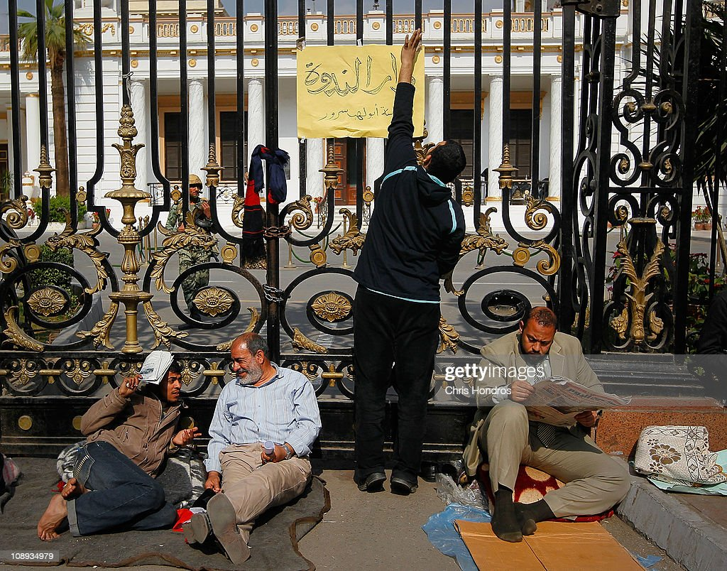 An anti-government protester attachs a sign to the gate of the Egyptian Parliament building while others sit against the gate after camping there overnight Feburary 9, 2011 in Cairo, Egypt. Thousands of Egyptians protested outside of the parliament building in downtown Cairo to demand the assembly's immediate dissolution as part of a wave of anti-government protests in the nearby Tahrir Square.