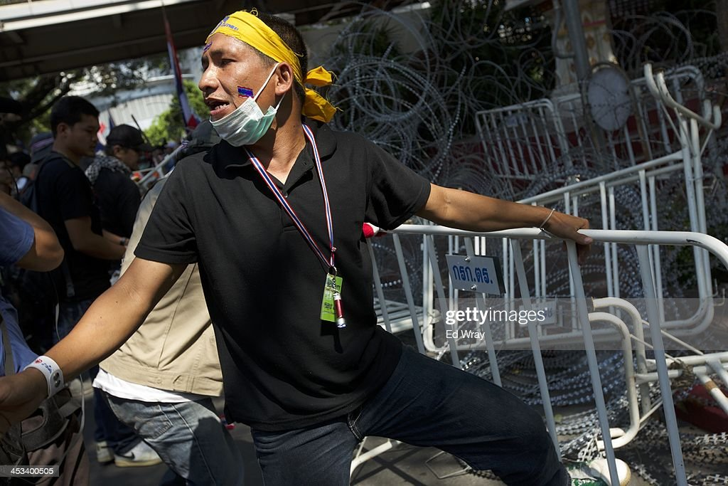 An anti-government protester calls for help while removing barbed wire and barricades in front of the central police headquarters during a demonstration on December 4, 2013 in Bangkok, Thailand. The protesters continued their demonstration, though in keeping with the relative calm after several days of violent clashes with police, there was no violence.
