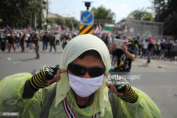 An antigovernment protester covers his ears during a demonstration near Government house in Bangkok Riot police fired tear gas at antigovernment mobs...