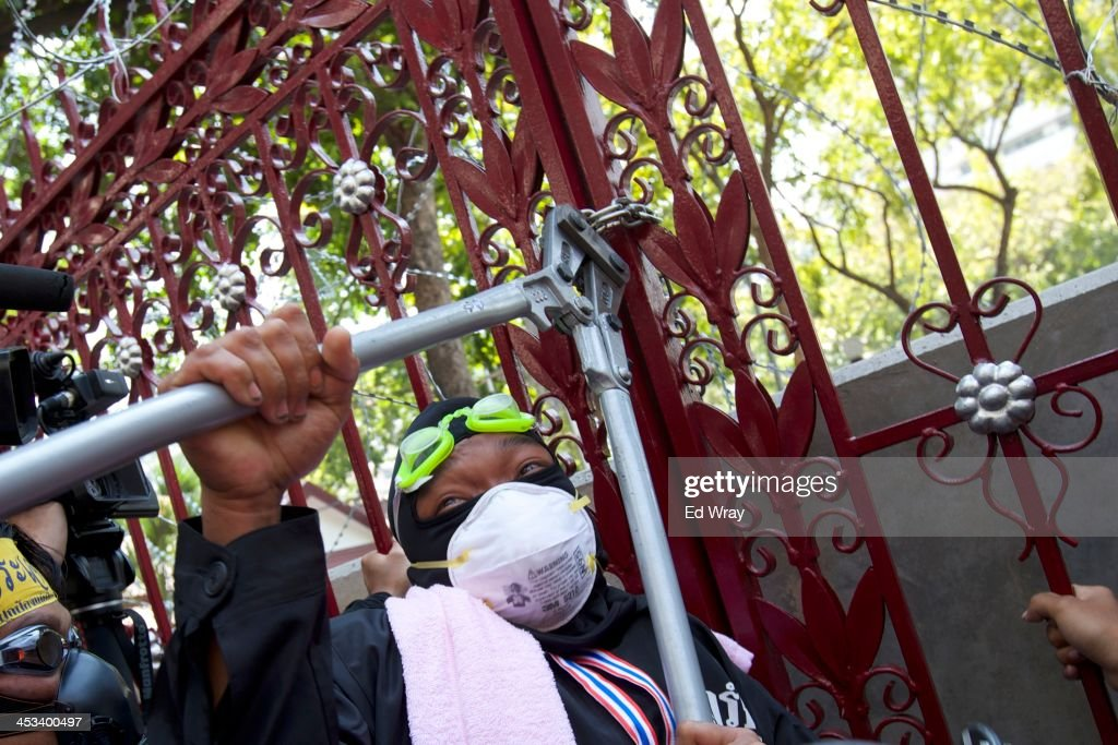 An anti-government protester cuts through a chain lock during an effort by the protesters to remove a barricade in front of the central police headquarters during a demonstration on December 4, 2013 in Bangkok, Thailand. The protesters continued their demonstration, though in keeping with the relative calm after several days of violent clashes with police, there was no violence.