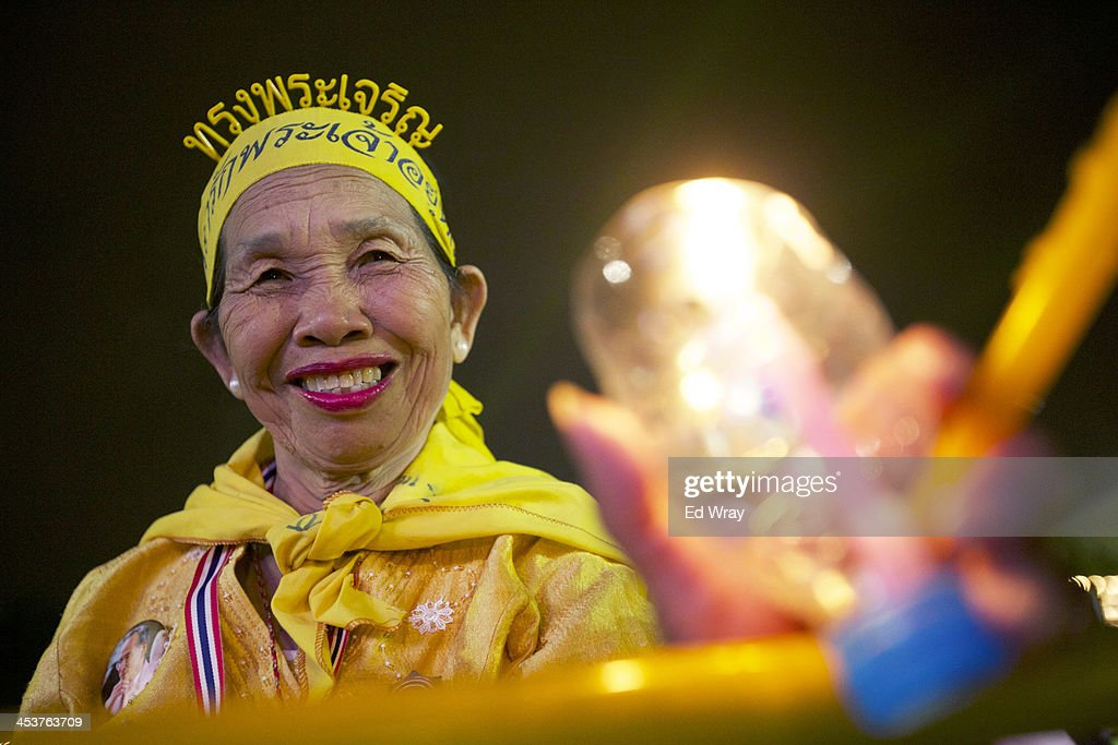 An anti-Government protester holds a candle during a mass celebration for the 86th birthday of Thai King Bhumibol Adulyadej, at the democracy monument which protesters have been occupying on December 5, 2013 in Bangkok, Thailand. The tension between police and anti-government protesters has calmed as the protesters have temporarily agreed to halt their activities to pay respect to the King on his birthday.