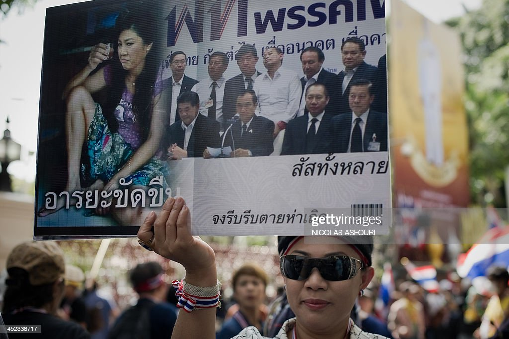 An anti-government protester holds a photograph mocking Thai Prime Minister Yingluck Shinawatra (L) in front of the national police headquarters during a demonstration in Bangkok on November 28, 2013. Thai opposition protesters cut the electricity supply to the national police headquarters, a senior officer said, ignoring a plea from Prime Minister Yingluck Shinawatra to end their rallies. AFP PHOTO/ Nicolas ASFOURI
