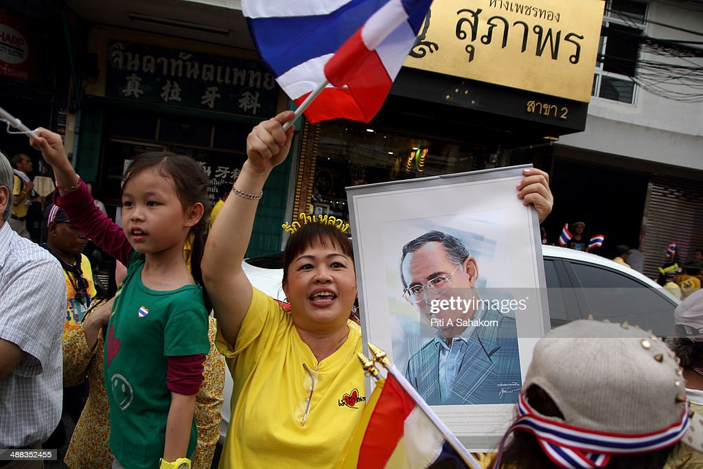 An anti-government protester holds a portrait of King Bhumibol Adulyadej during a rally showing their loyalty to King Bhumibol Adulyadej on the 64th anniversary of his Coronation Day. Thailand's revered King Bhumibol Adulyadej made a rare public appearance to mark the 64th anniversary of his coronation. Thailand's Election Commission and the caretaker government agreed to hold new elections on 20 July 2014 after several months of political turmoil and uncertainty while anti-government protesters calling the resignation of caretaker Prime Minister Yingluck Shinawatra and demanding political reforms before any new elections.