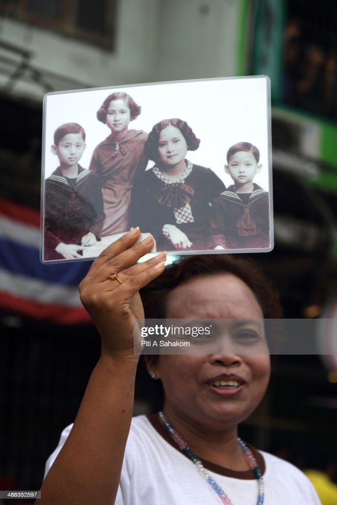 An anti-government protester holds a portrait of members of the Royal Family during a rally showing their loyalty to King Bhumibol Adulyadej on the 64th anniversary of his Coronation Day. Thailand's revered King Bhumibol Adulyadej made a rare public appearance to mark the 64th anniversary of his coronation. Thailand's Election Commission and the caretaker government agreed to hold new elections on 20 July 2014 after several months of political turmoil and uncertainty while anti-government protesters calling the resignation of caretaker Prime Minister Yingluck Shinawatra and demanding political reforms before any new elections.