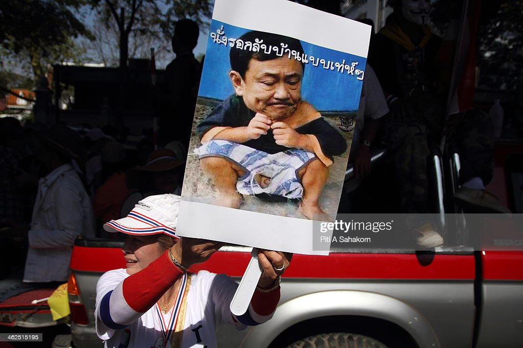 An anti-government protester holds a portrait of Thaksin Shinawatra during a rally at Rajprasong intersection in Bangkok. Major intersections were blocked in Thailand's capital as protesters began a 'Bangkok shutdown' campaign to force out the government of caretaker Prime Minister Yingluck Shinawatra. Thai anti-government protesters said they would set up protest camps at seven main intersections in Bangkok in their bid to paralyse the capital. Protest leader Suthep Thaugsuban said 'We will do it all days and we will do it everyday until we win''.