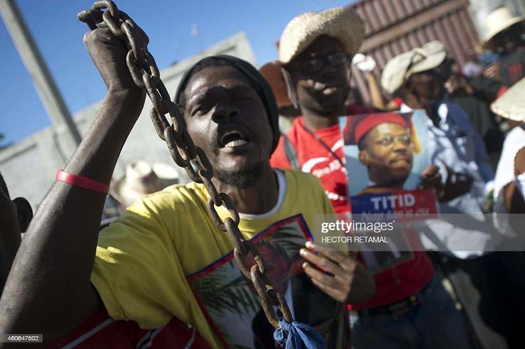An antigovernment protester holds a poster with the photo of former Haitian president JeanBertrand Aristide and chains while performing a voodoo...