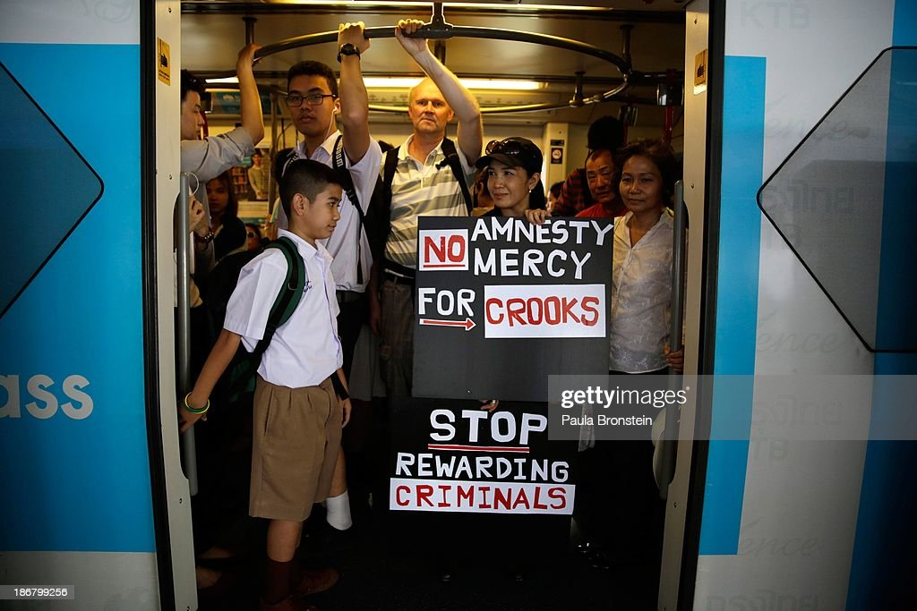 An anti-government protester holds signs as she heads off on a sky train after a rally against a controversial Amnesty bill which was passed in Parliament last week on November 4, 2013 in Bangkok, Thailand. Thousands attended various protests around the capitol city organised by the opposition Democrat Party. If the law goes into effect protestors fear it could whitewash all crimes for which the billionaire former leader Thaksin Shinawatra was convicted, setting the stage for him to return to Thailand.