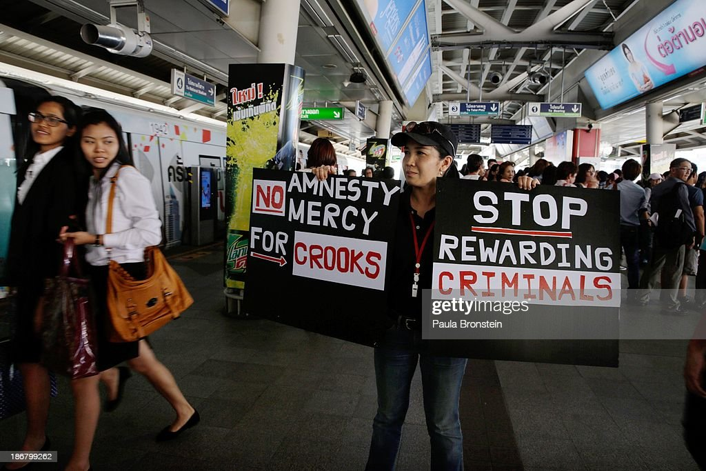 An anti-government protester holds signs at the sky train station after a rally against a controversial Amnesty bill which was passed in Parliament last week on November 4, 2013 in Bangkok, Thailand. Thousands attended various protests around the capitol city organised by the opposition Democrat Party. If the law goes into effect it whitewash all crimes for which the billionaire former leader Thaksin Shinawatra was convicted, setting the stage for him to return to Thailand.