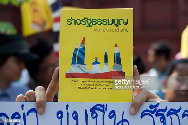 An antigovernment protester holds the official Thai constitution book during a rally outside the parliament building in Bangkok on February 23 2012...