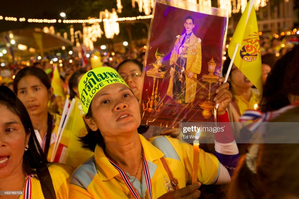 An anti-Government protester holds up a picture of the Thai King Bhumibol Adulyadej as prayers are said during a mass celebration of his 86th birthday at the democracy monument which protesters have been occupying on December 5, 2013 in Bangkok, Thailand. The tension between police and anti-government protesters has calmed as the protesters have temporarily agreed to halt their activities to pay respect to the King on his birthday.