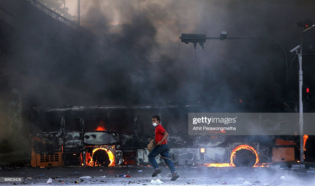An anti-government protester runs past a bus torched by supporters of former Prime Minister Thaksin Shinawatra during a protest on April 13, 2009 in Bangkok, Thailand. Anti-government protesters clashed with the military on the streets of Thailand's capital after the government declared a state of emergency. The pro-Shinawatra demonstrators are calling for the resignation of Prime Minister Abhisit Vejjajiva and for fresh elections to be held.