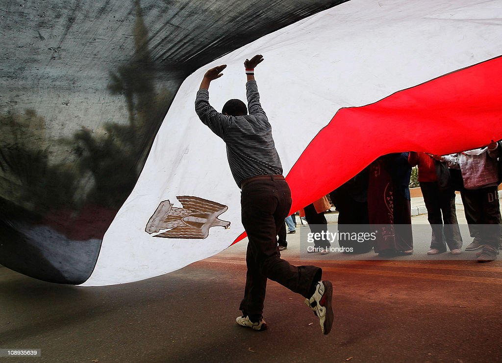 An anti-government protester runs under a large Egyptian flag in front of the Egyptian Parliament building Feburary 9, 2011 in Cairo, Egypt. Thousands of Egyptians protested outside of the parliament building in downtown Cairo to demand the assembly's immediate dissolution as part of a wave of anti-government protests in the nearby Tahrir Square.