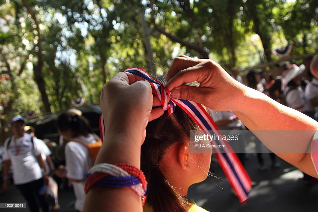 An anti-government protester ties a Thai national flag bow on her child during a rally at Rajprasong intersection in Bangkok. Major intersections were blocked in Thailand's capital as protesters began a 'Bangkok shutdown' campaign to force out the government of caretaker Prime Minister Yingluck Shinawatra. Thai anti-government protesters said they would set up protest camps at seven main intersections in Bangkok in their bid to paralyse the capital. Protest leader Suthep Thaugsuban said 'We will do it all days and we will do it everyday until we win''.