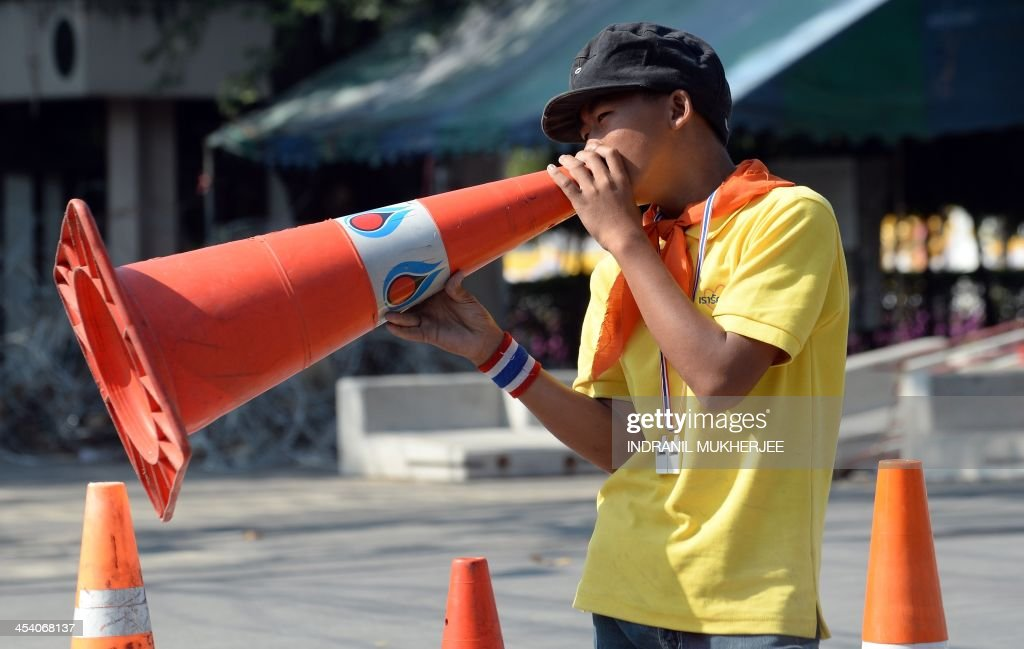 An anti-government protester uses a traffic cone as a megaphone to speak to colleagues at a distance, near the Government House in Bangkok on December 7, 2013. The leader of mass opposition protests that have shaken the Thai capital called Friday for a last-ditch effort to topple the government, vowing to surrender to the authorities if the action fails. With turnout dwindling after more than a month of rolling ralliesand violence that left five people dead and more than 200 injured, the former deputy premier spearheading the movement gave the first indication that he might concede defeat unless enough people join the protest on Monday, describing it as 'judgment day'. AFP PHOTO/Indranil MUKHERJEE