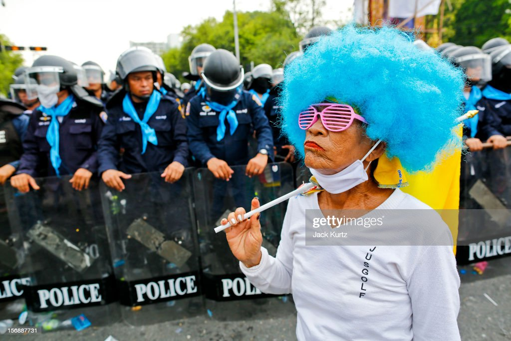 An anti-government protester walks past ranks of Thai riot police during a large anti government protest on November 24, 2012 in Bangkok, Thailand. The Siam Pitak group, which sponsored the protest, cited alleged government corruption and anti-monarchist elements within the ruling party as grounds for the protest. Police used tear gas and baton charges againt protesters.
