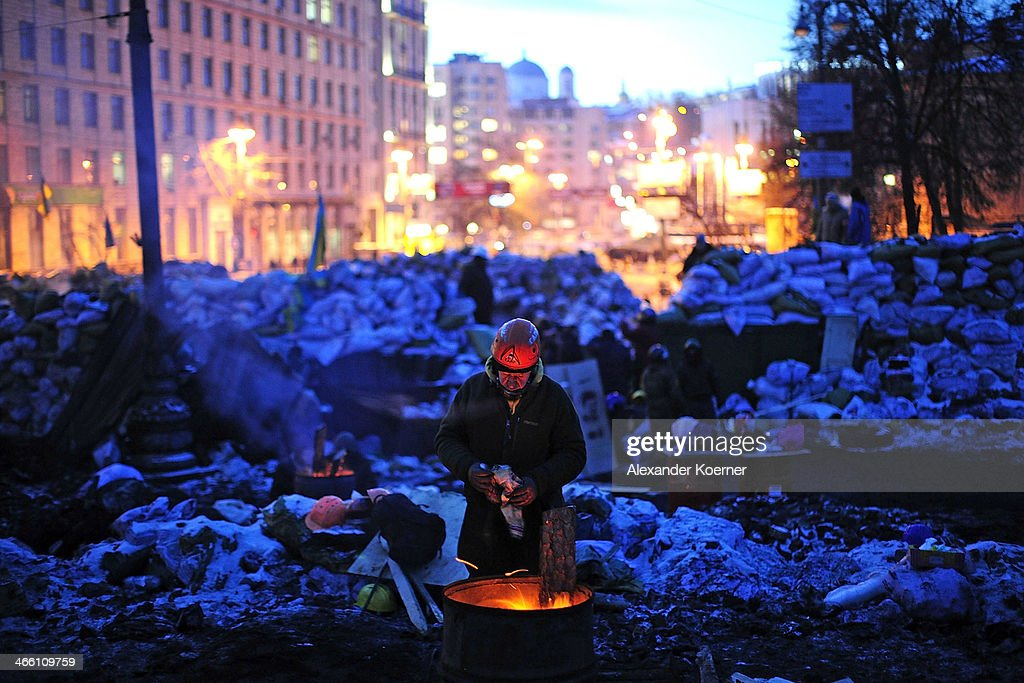An anti-government protester warms himself at a fireplace at a barricade on Hrushevskoho Street on January 31, 2014 in Kiev, Ukraine. Ukraine's Prime Minister Mykola Azarov and his cabinet resigned three-days ago following months of protests, while parliament is also scrapping a number of controversial anti-protest laws.