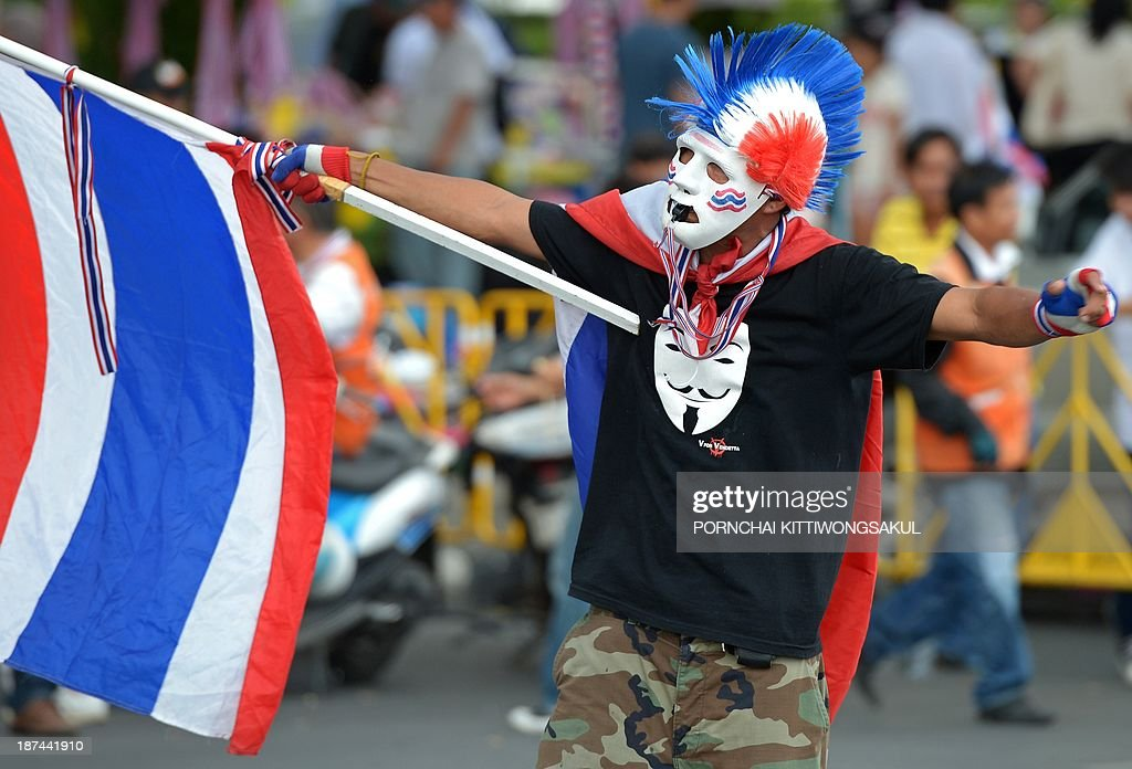 An anti-government protester waves a national flag during a rally against an amnesty bill at Democracy monument in Bangkok on November 9, 2013. Thai anti-government protesters gathered in Bangkok seeking to raise pressure on the Thai government over its controversial political amnesty bill.