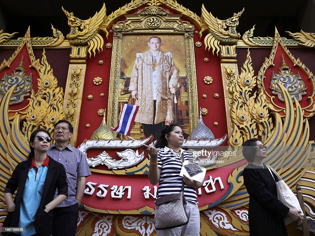 An anti-government protester waves a Thai flag in front of a portrait of the Thai King during rally against a controversial Amnesty bill that passed in Parliament last week in Bangkok, Thailand on November 4, 2013. Thousands attended various protests around the capitol city organised by the opposition Democrat Party. If the law goes into effect protestors fear it could whitewash all crimes for which the billionaire former leader Thaksin Shinawatra was convicted, setting the stage for him to return to Thailand.