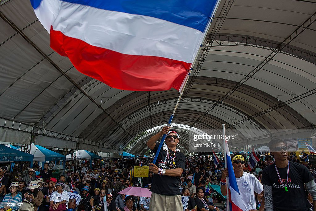 An Anti-government protester waves national flag during a rally at Democracy Monument on November 30, 2013 in Bangkok, Thailand. Anti-government protesters in Bangkok say they plan to occupy the government house and the zoo, demonstrators calling on the government to step down have marched on ministries and government bodies in an attempt to shut them down.