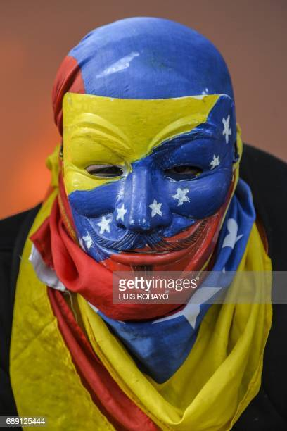 An antigovernment protester wearing a mask with the national flag takes part in a roadblock on the Francisco Fajardo highway in Caracas during a...