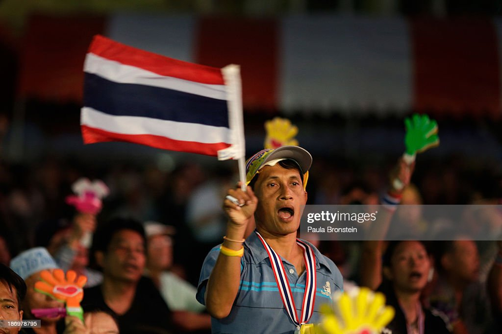 An anti-government protestor waves a Thai flag during rally against a controversial amnesty bill that passed in Parliament last week on November 5, 2013 in Bangkok, Thailand. Thousands attended various protests around the capitol city organized by the opposition Democrat Party. If the law goes into effect it will whitewash all crimes against the billionaire, former leader Thaksin Shinawatra setting the stage for him to return to Thailand.