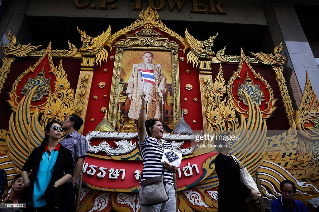 An anti-government protestor waves a Thai flag in front of a portrait of the Thai King during rally against a controversial Amnesty bill that passed in Parliament last week on November 4, 2013 in Bangkok, Thailand. Thousands attended various protests around the capitol city organised by the opposition Democrat Party. If the law goes into effect protestors fear it could whitewash all crimes for which the billionaire former leader Thaksin Shinawatra was convicted, setting the stage for him to return to Thailand.