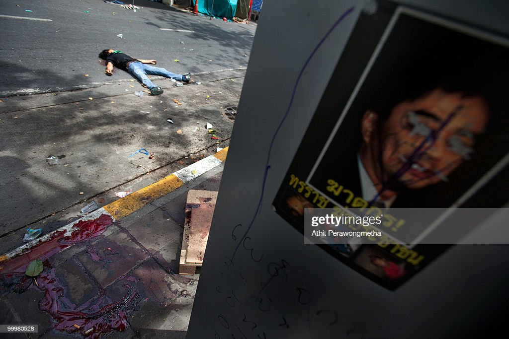 An anti-government Red Shirt protester lies dead on the street inside their encampment on May 19, 2010 in Bangkok, Thailand. At least 5 people are reported to have died as government forces sought to overrun barricades raised in and around the city centre by anti-government protestors. Red-shirt leaders have now surrendered, ending their blockade in the aftermath of a sixth day of violence, leaving the army in control and a night time curfew to be imposed.