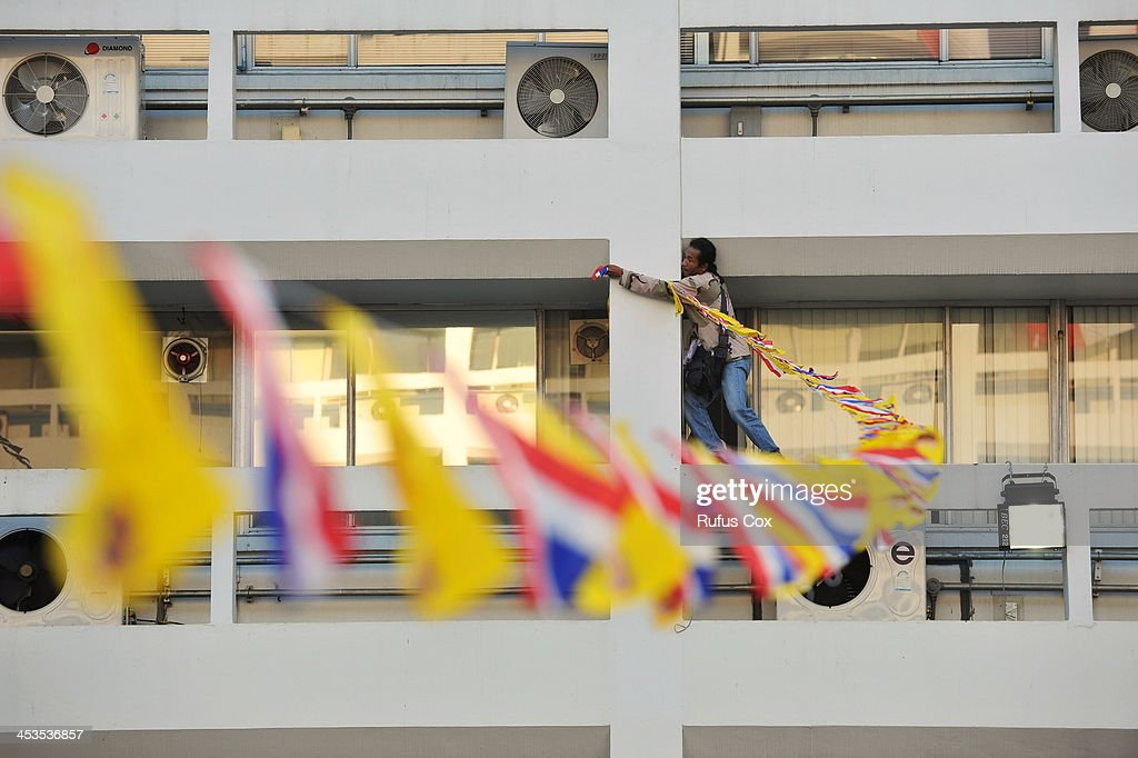 An anti-government ties royal and Thai national flags to span builings in the Ministry of Finance compound in marking the birthday of the Thai monarch King Bhumibol Adulyadej on December 4, 2013 in Bangkok, Thailand. Protesters have occupied the ministry for nine days. In marking the king's 86th birthday on Thursday, the protesters have declared a temporary truce in their campaign to topple the government.