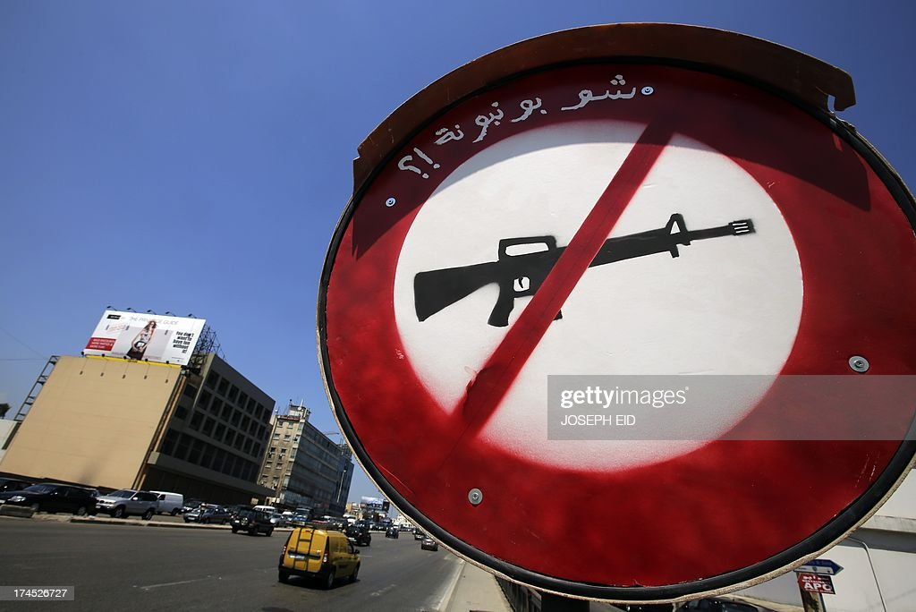An anti-gun sign reading in Arabic 'it's not a lollipop' stands on the side of a road at the northern entrance of Beirut on July 27, 2013. AFP PHOTO/JOSEPH EID