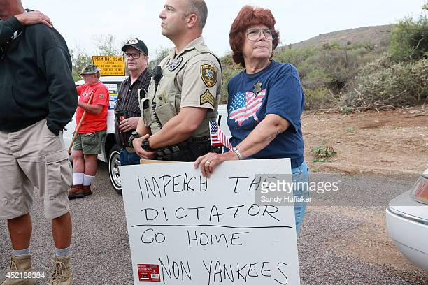 An antiimmigration activist stands next to a Pinar County Sheriff's deputy during a protest along Mt Lemmon Road in anticipation of buses carrying...