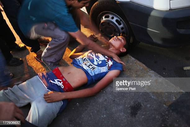 An antiMohammed Morsi protester is attended to after as he lays motioneless after allegedly being shot by Muslim Brotherhood supporters in Tahrir...