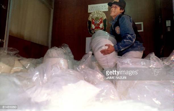 An antinarcotics policeman lifts a bag of cocaine in Lima 27 August 1993 captured during an antidrug operation in connection with the Cali drug...