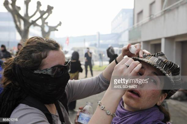 An antiNATO protester helps another to treat the effects of tear gas during a demonstration on April 4 2009 in Strasbourg eastern France French riot...