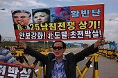 An AntiNorth Korean protester holds up a banner at a checkpoint on the Unification Bridge leading to the Kaesong Industrial complex and North Korea...