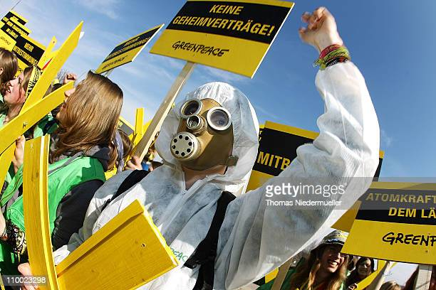 An antinuclear activist wearing a gas mask protests together with other activists in front of the Neckarwestheim nuclear power plant on March 12 2011...