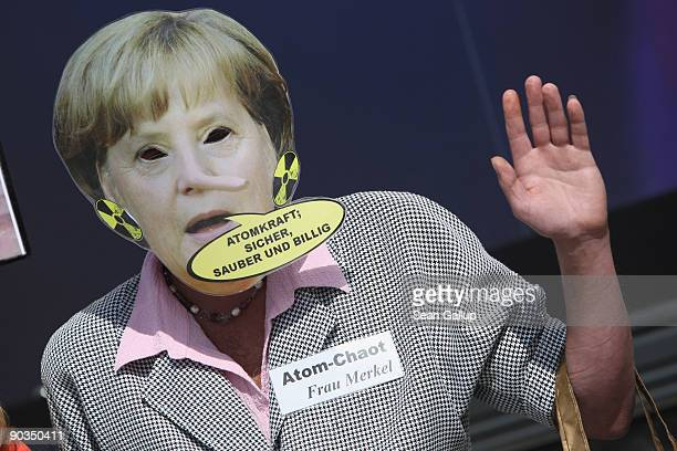 An antinuclear protester dressed as German Chancellor and Christian Democrat Angela Merkel and wearing a bubble that reads 'Nuclear Power Safe Clean...