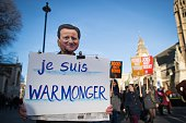 An antinuclear protester wearing a mask depicting British Prime Minister David Cameron holds a sign that reads 'I am warmonger' during a protest in...