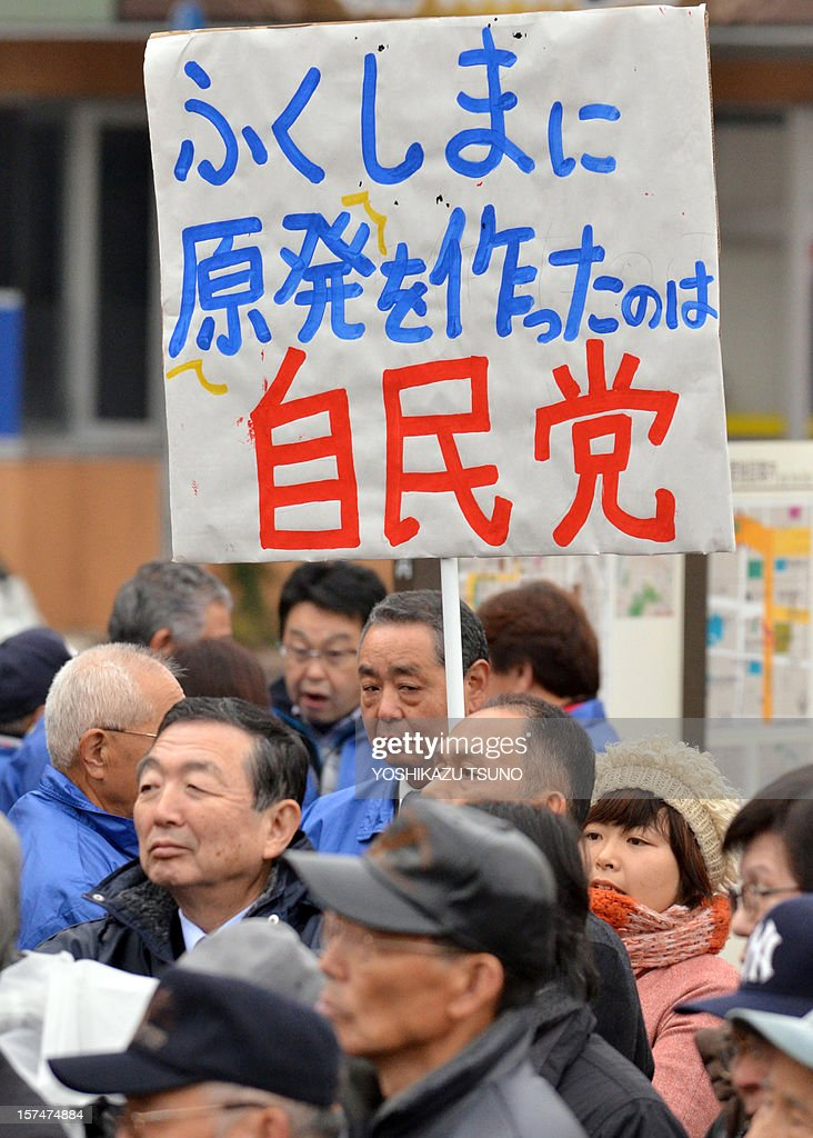 An anti-nuclear protestor (R in pick coat) displays a placard saying 'Liberal Democratic party (LDP) built nuclear plants in Fukushima', behind supporters of the LDP as main opposition leader Shinzo Abe holds a meeting to support party candidate Yoshitami Kameyama at Fukushima, northern Japan on December 4, 2012. Campaigning officially started ahead of Japan's December 16 general election. AFP PHOTO / Yoshikazu TSUNO