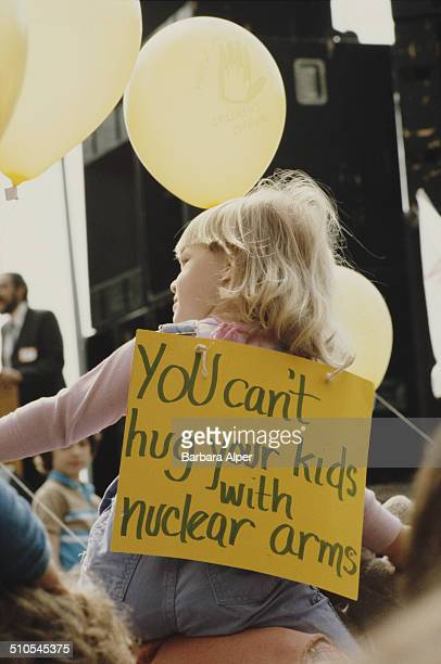 An antinuclear rally in New York City 12th June 1982 A child wears a sign reading 'You can't hug your kids with nuclear arms'