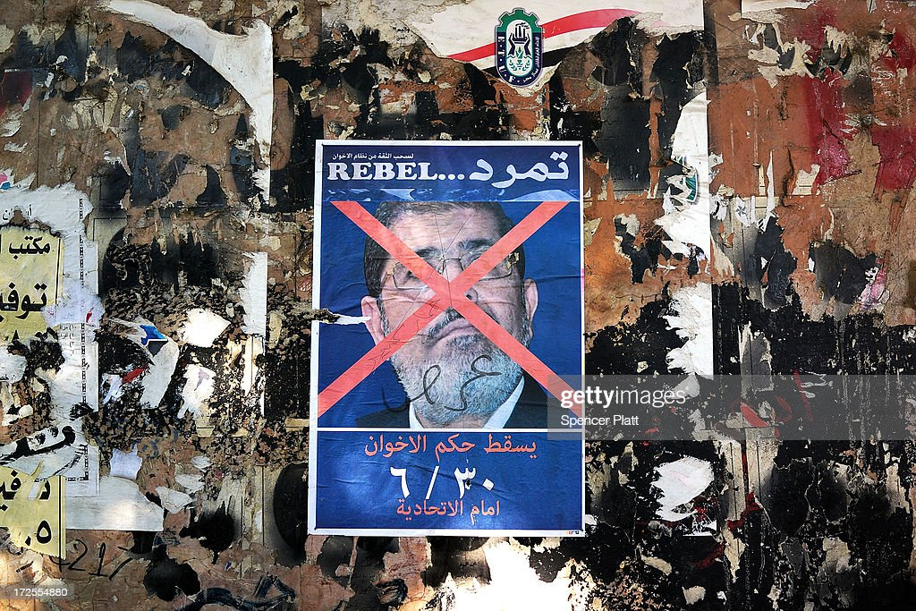 An anti-President Mohammed Morsi poster is viewed as as thousands of Egyptian protesters celebrate in Tahrir Square as the deadline given by the military to Egyptian President Mohammed Morsi passes on July 3, 2013 in Cairo, Egypt. The president gave a defiant speech last night and vowed to stay in power despite the military threats. As unrest spreads throughout the country, at least 23 people were killed in Cairo on Tuesday and over 200 others were injured. It has been reported that the military has taken over the state television.