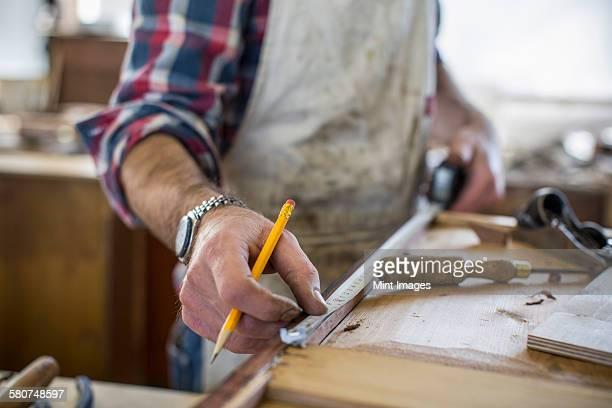 An antique furniture restorer measuring a piece of wood.