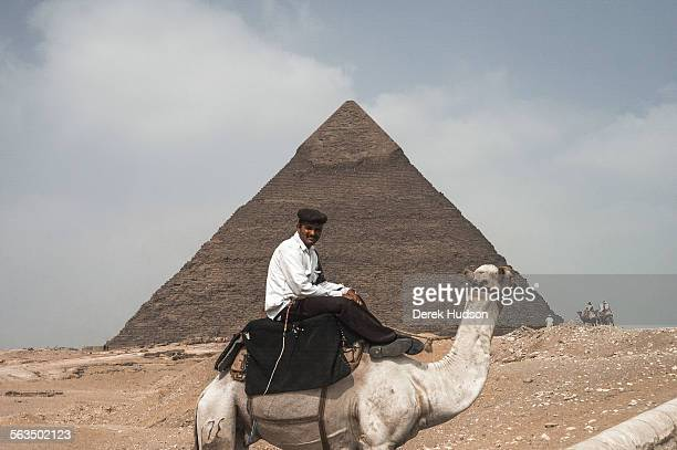 An antiquities police officer on camelback with the Khafre Pyramid' the second largest of the three on the site at Giza in the background