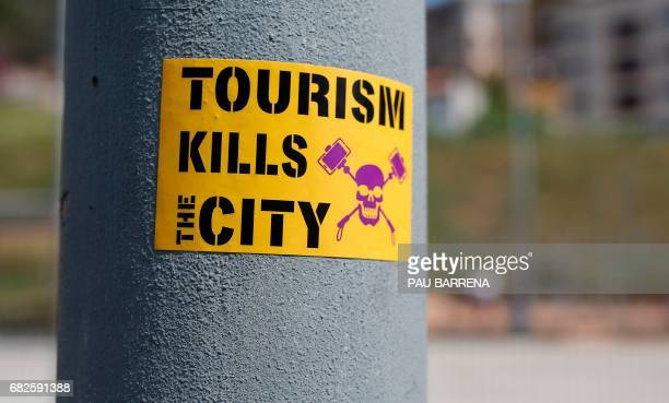 An antitourism sticker is pictured near Park Guell at the Vallcarca neighborhood on May 13 2017 in Barcelona / AFP PHOTO / PAU BARRENA