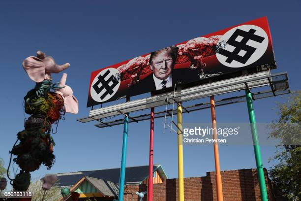 An antiTrump billboard displaying swastikalike dollar signs stands near the corner of Grand Ave and Taylor Street on March 21 2017 in Phoenix Arizona...