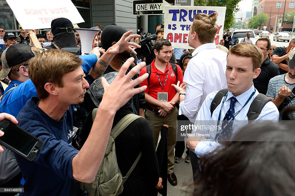 An anti-Trump protestor and a Trump supporter clash outside the Western Conservative Summit on July 1, 2016.