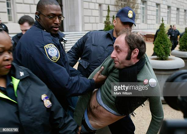 An antiwar protester gets arrested after jumping over a police barricade in front of the Internal Revenue Service Building March 19 2008 in...